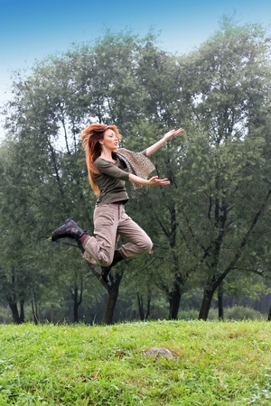 The girl jumps on a grass and trees as a background photo