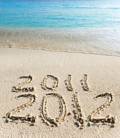 On sand at ocean edge it is written 2011-2012 photo