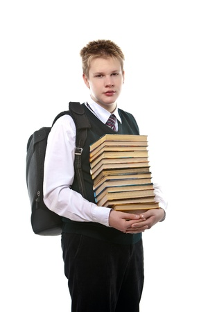 The schoolboy in a school uniform with a huge pack of books photo