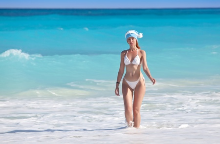 The girl in a hat of Santa Claus leaves the sea   photo