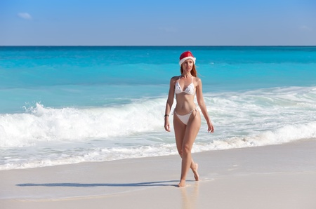 The young woman in a hat of Santa Claus goes on a beach at sea edge   photo