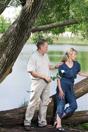 The man and the woman near the lake. Quarrel. Reconciliation attempt. photo