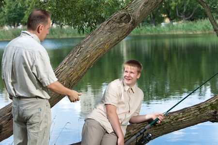 The father asks a fishing tackle from the son too to fish photo