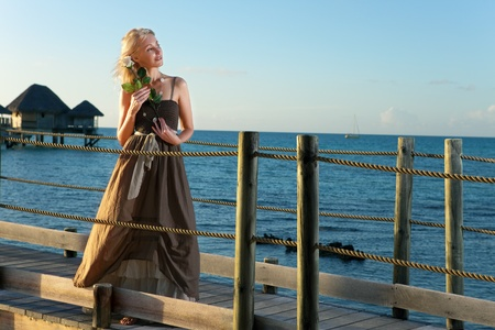 The young beautiful woman with a rose on a wooden path at the sea, tropics