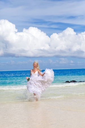 The young beautiful woman in a dress of the bride runs on waves of the sea   photo