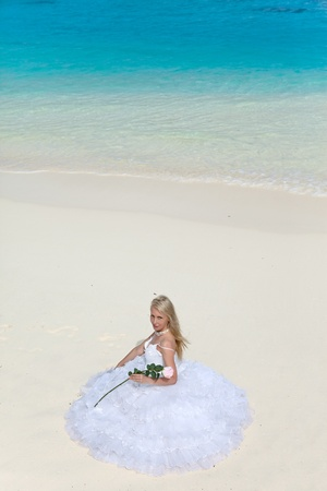 The young beautiful woman in a dress of the bride sits on sand at sea edge photo