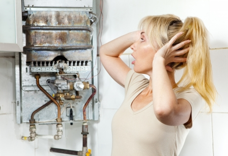 malfunction: The young woman is upset by that the gas water heater has broken