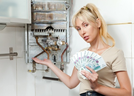 money to burn: The sad woman the housewife counts up money for repair of a gas water heater   Stock Photo