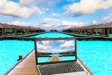 Wooden road  over the sea and the laptop with a beach picture   photo