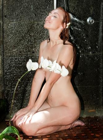 Girl under shower in the garden photo