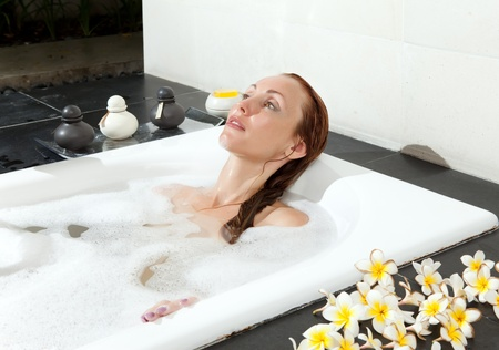 lying in bathtub: woman lays in soapsuds in bathing, full water