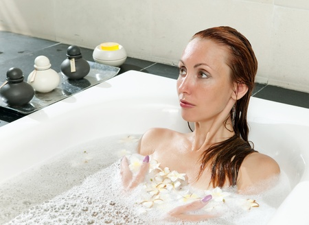woman lays in soapsuds in bathing, full water   photo