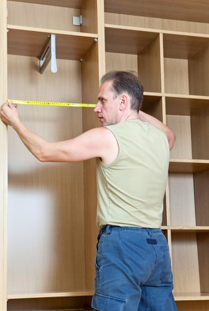 assemblage: The man is engaged in assemblage of a new wardrobe