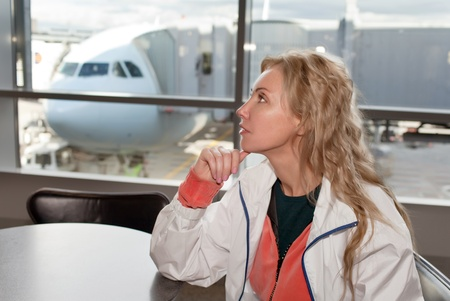 The airport. A waiting room. The woman at a window and the plane on a background.