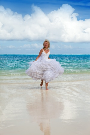 borabora: The young beautiful woman in a dress of the bride runs on waves of the sea