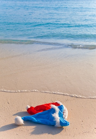 Two New Years caps of Santa Claus on beach photo