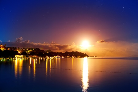 Night. The moon over the sea and reflection in water. Bora-Bora photo
