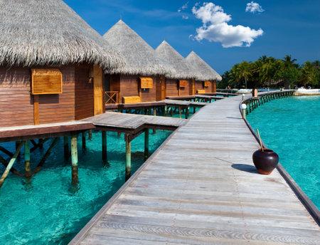 Island in ocean, Maldives.  Villa on piles on water