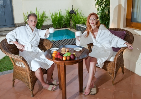 Young attractive couple drinks tea near the pool photo