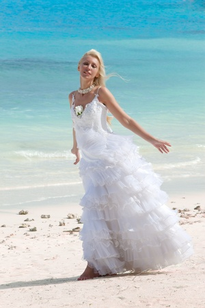 borabora: The young beautiful woman in a dress of the bride standing at sea edge