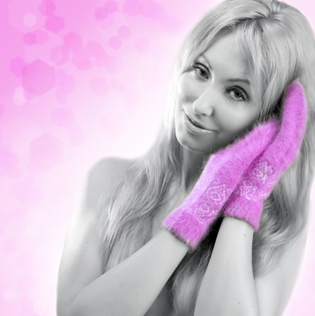 The young woman in pink mittens on an abstract background photo