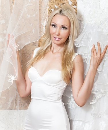 ruching: The young woman near to a wedding dress dreams of wedding