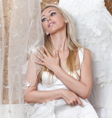 The girl near to a wedding dress dreams of wedding Stock Photo