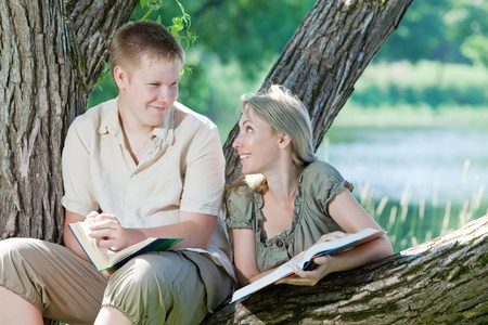 Young guy and girl with books on the nature near lake photo
