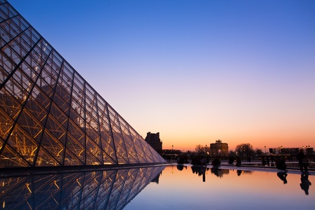 PARIS - MARCH 14: Louvre Pyramid and a view on a Tuileri garden, sunset, March 14, 2012 in Paris, France.
