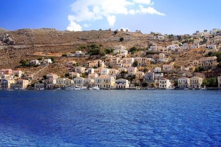 Greece. Dodecanesse. Island Symi (Simi). Colorful houses on rocks.   photo