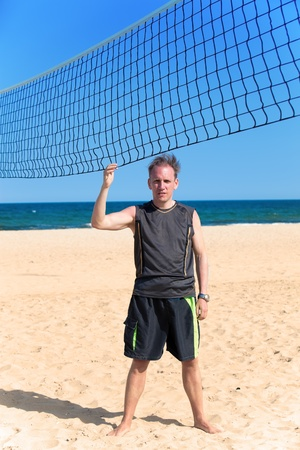 The sporting man near a grid for beach volleyball Stock Photo - 13183527