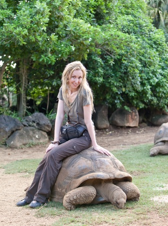 young beautiful tourist woman riding  on giant turtle in La Vanille Reserve park photo