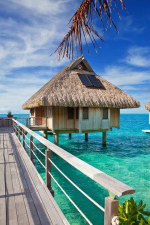 바다 물 위에 오두막 목조 다리