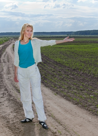 The young woman on the rural road shows a hand in the field with the first sprouts photo