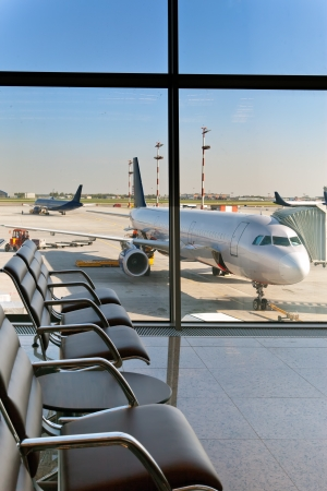 Empty armchairs in hall of expectation of airport and plane behind window   Stock Photo