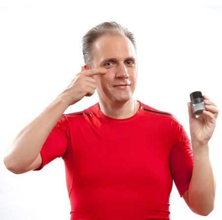 appearance: The mature well-groomed man cares of the appearance - uses  against wrinkles cream
