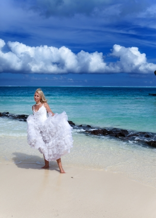 The young beautiful woman in a dress of the bride  at edge of the sea  photo
