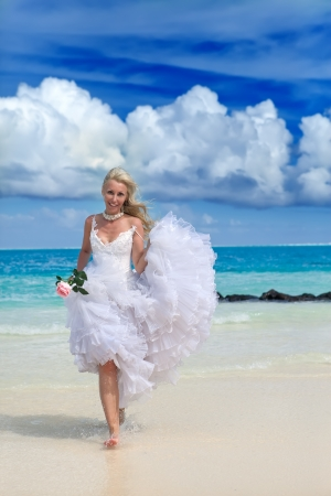 The young beautiful woman in a dress of the bride  at edge of the sea with a rose in a hand   photo