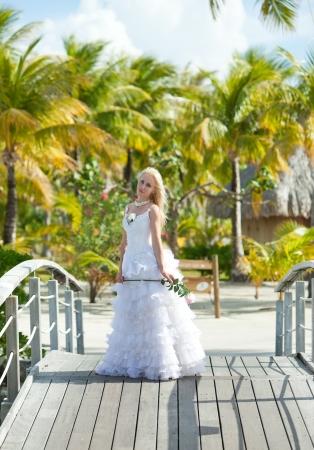 borabora: The young beautiful woman in a dress of the bride on the bridge about sea edge. Polynesia. Bora-Bora   Stock Photo