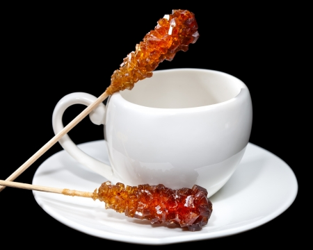 Coffee cup and  candy sugar on a stick photo