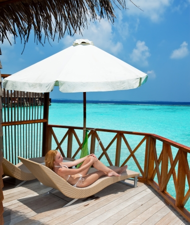 Young woman tans on a terrace of water villa on ocean Maldives photo
