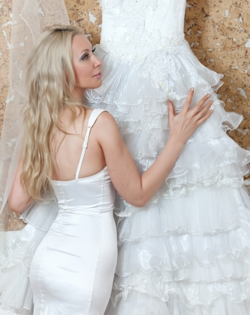 ruching: The young woman with a wedding dress in hands dreams of wedding   Stock Photo