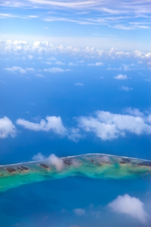 The atoll ring in ocean is visible through clouds. Aerial view.   photo