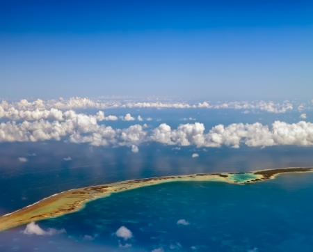 Polynesia  The atoll ring in ocean is visible through clouds  Aerial view  photo
