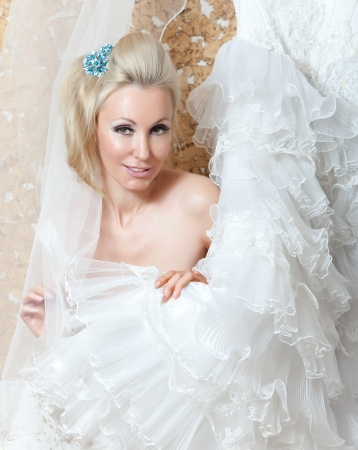 The young woman with a wedding dress in hands dreams of wedding   Stock Photo