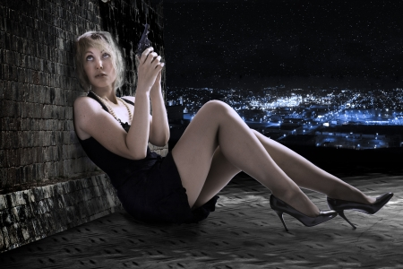 mujer con pistola: La mujer joven con el arma en una azotea. Noche. Foto de archivo