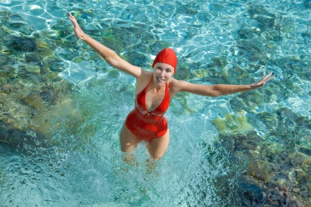 bathing   suit: The girl in a red bathing suit jumps out of the sea