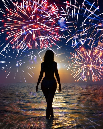 Festive fireworks over the sea and a silhouette of the woman going in waves   photo