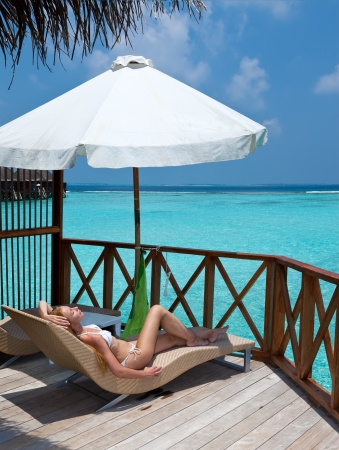Young woman tans on a water villa terrace , Maldives photo