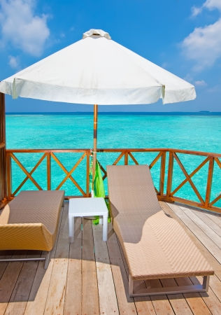 lounges: Parasol and chaise lounges on a terrace of water villa, Maldives Stock Photo